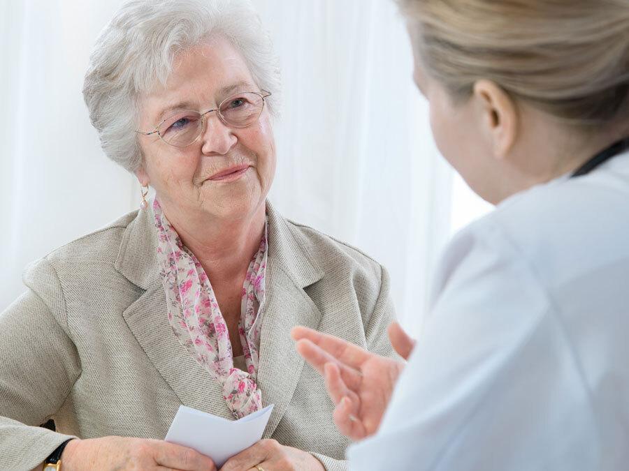 Eine ältere Dame spricht mit Ihrer Hausärztin. Sie hat sich Fragen zur Patientenverfügung notiert.