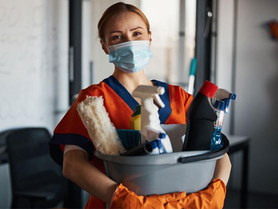 Eine Hausmeisterin hält Putzmaterial in den Händen.