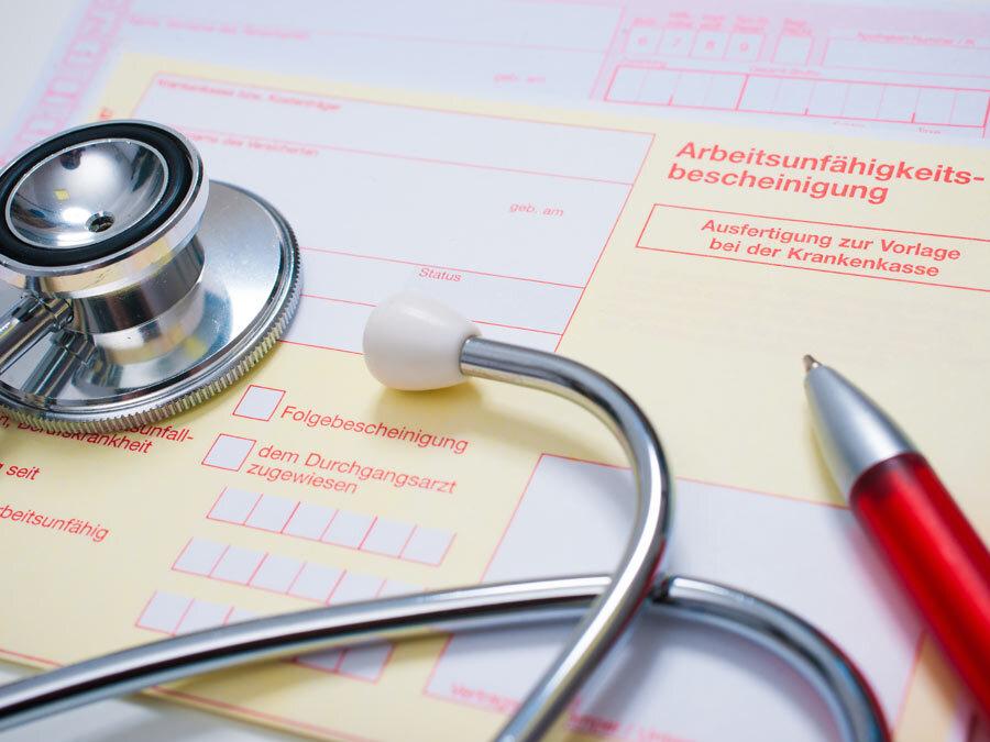 Eine Arbeitsunfähigkeitsbescheinigung liegt auf dem Tisch. Der Arbeitgeber möchte die Krankschreibung prüfen.