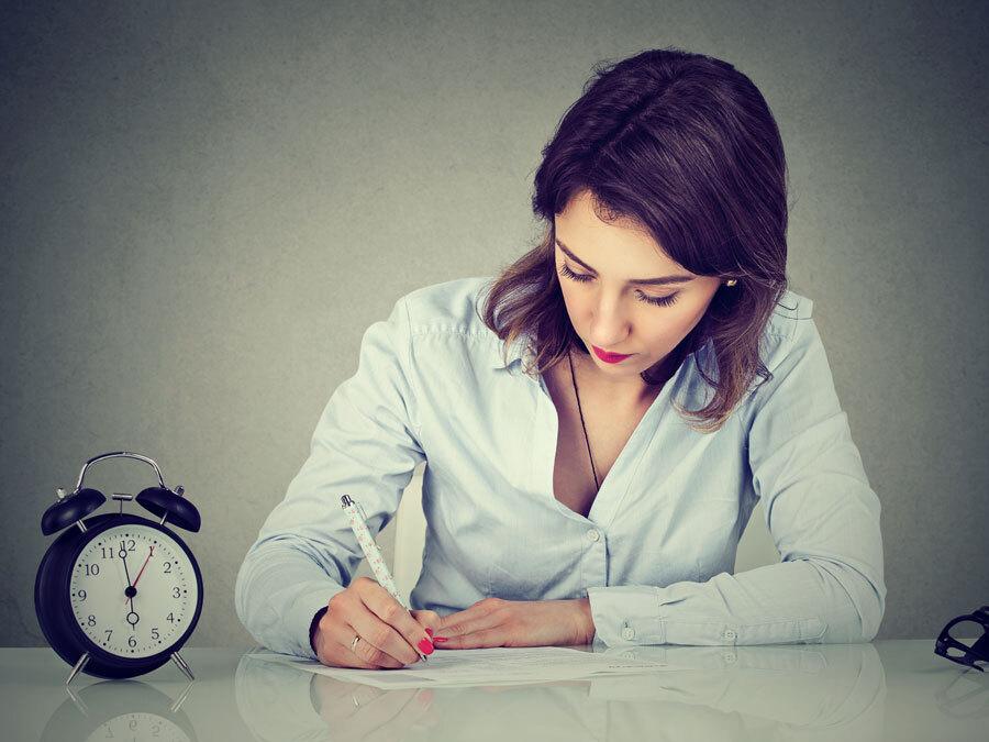 Eine Frau sitzt arbeitend an einem Schreibtisch. Neben ihr tickt ein Wecker und symbolisiert, dass sie sich noch in der Probezeit befindet.