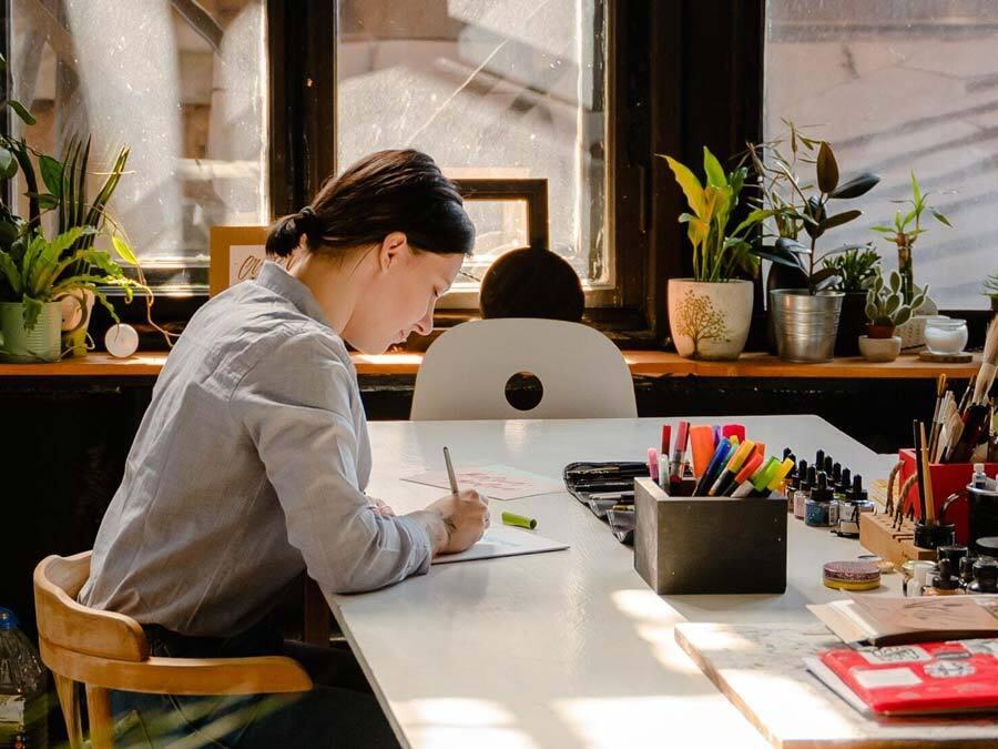 Ein Frau sitzt an einem sonnigen Schreibtisch und schreibt einen Urlaubsantrag.