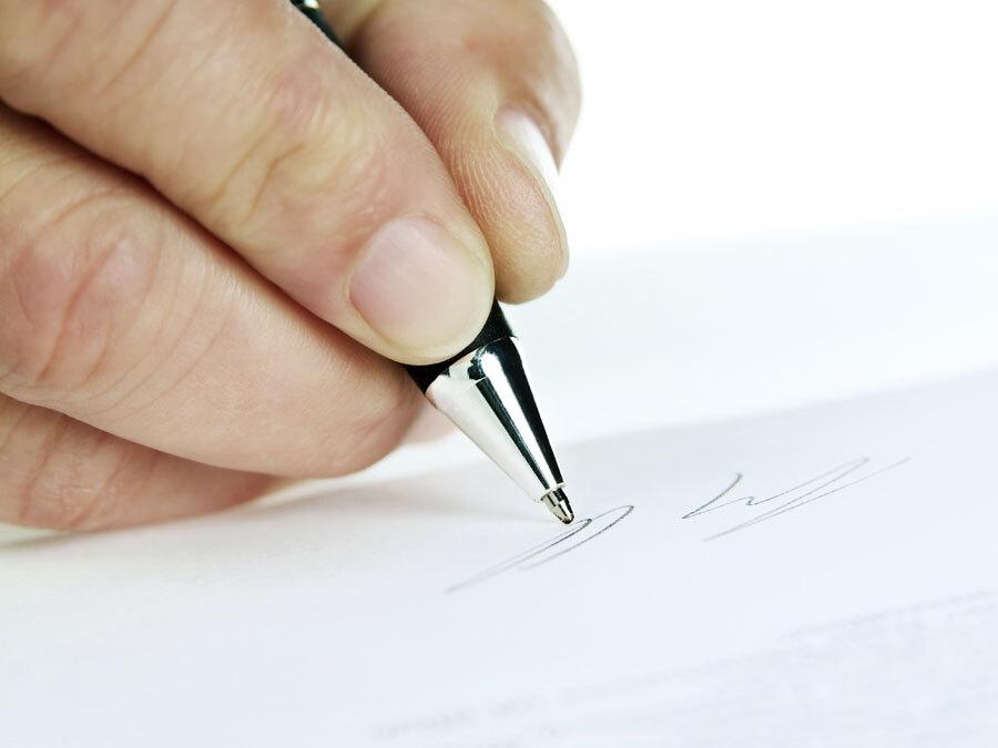 Wir sehen eine Hand mit einem Stift. Eine Person unterzeichnet gerade eine Untervollmacht.