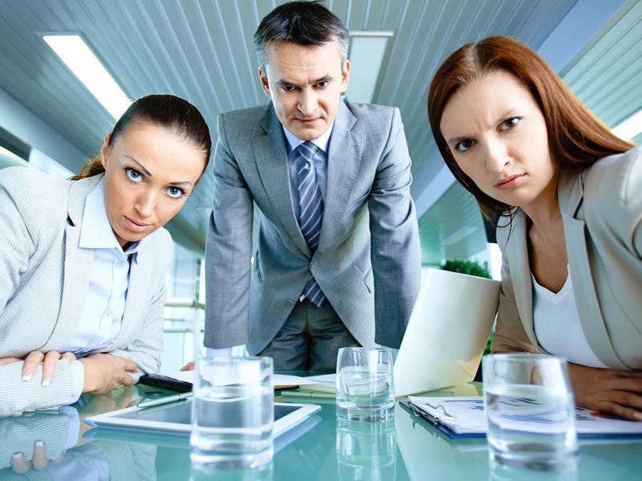 Drei Büroangestellte, mit verärgertem Blick schauen in die Kamera.