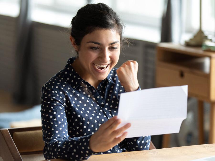 Eine Frau hält einen Brief in der Hand und freut sich. Ihre Bitte um eine Gehaltserhöhung hat Gehör gefunden.