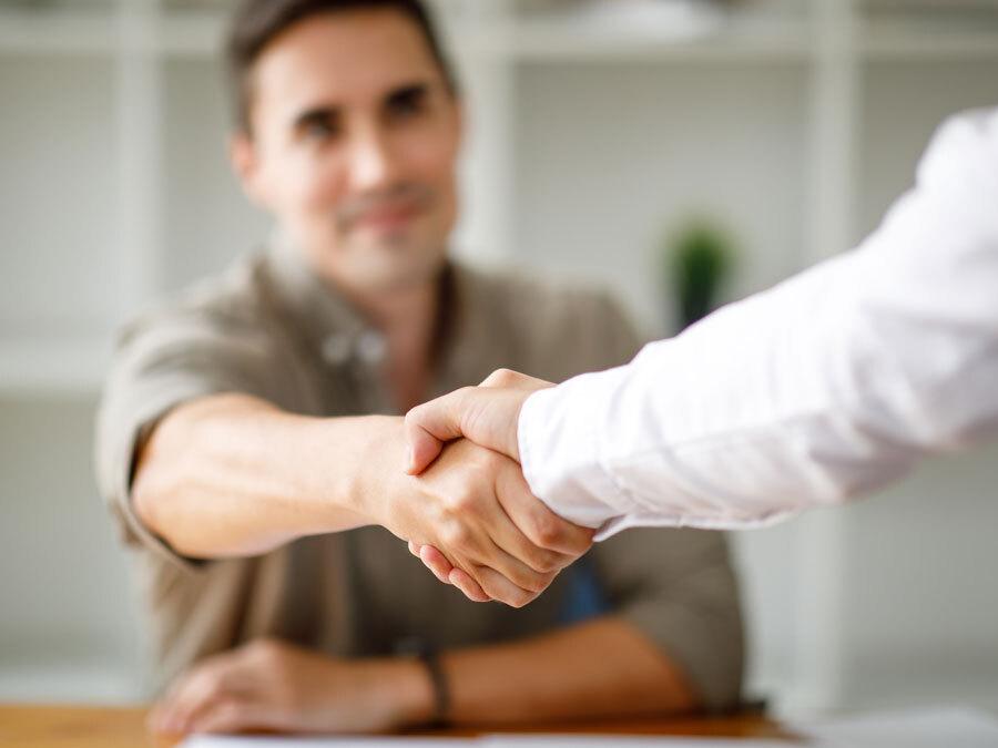 Ein Handshake bei Gehaltsverhandlungen zwischen Arbeitnehmer und Arbeitgeber.
