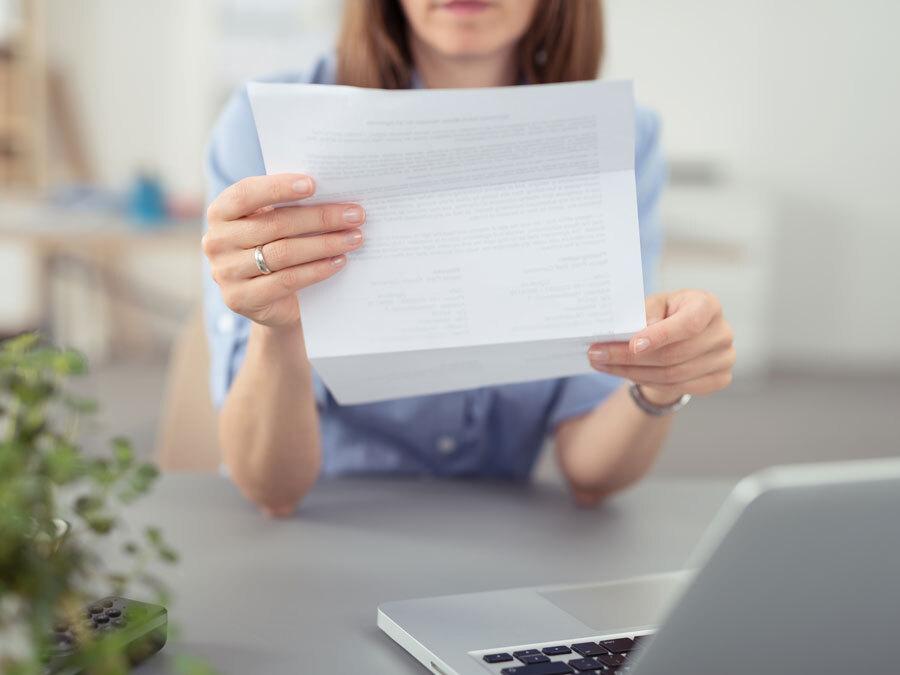 Eine Frau hält einen ernsten Brief in den Händen. Es ist eine Mahnung wegen Zahlungsverzug.