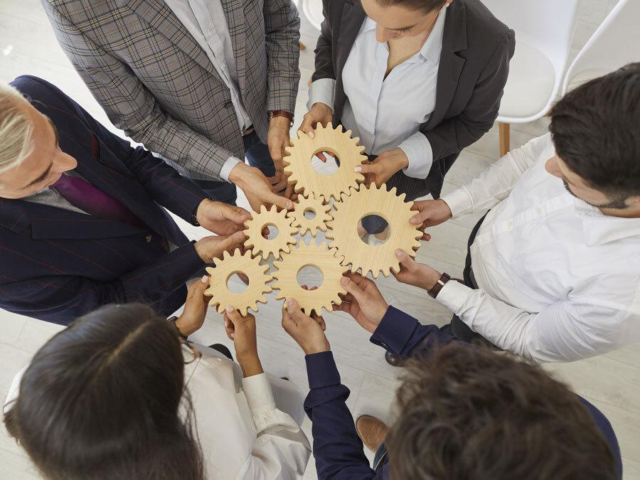 Mehrere Unternehmer halten Zahnräder in den Händen. Sie symbolisieren Managementsysteme.